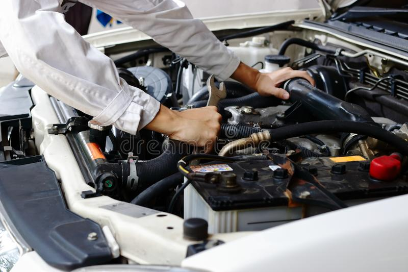 Hands of auto mechanic man with wrench repairing engine of motor under car hood. Insurance concept. Hands of auto mechanic man with wrench repairing engine of stock image