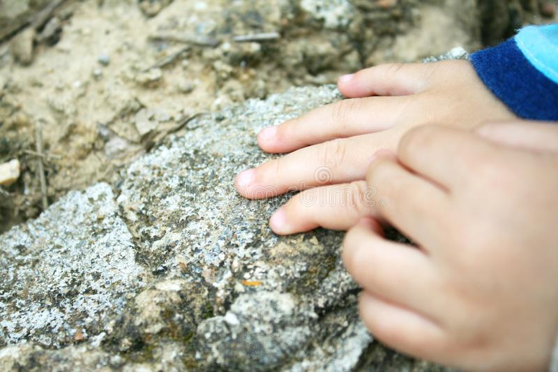 Hands of baby girl on rock royalty free stock photo