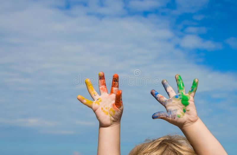 Hands of baby paint against blue sky royalty free stock image