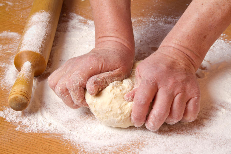 Hands of the baker knead a piece dough stock photos