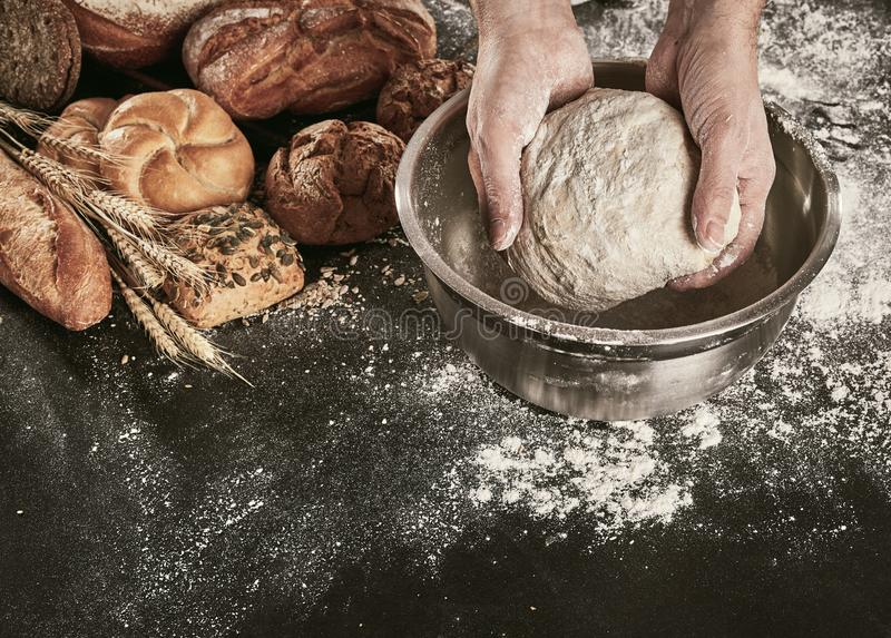 Hands of a baker kneading dough in a bowl royalty free stock photo