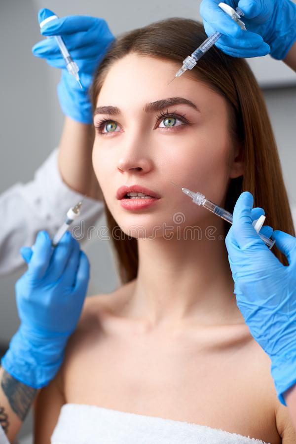 Hands of beauticians holding syringes around doll like woman face ready for injection in cosmetology clinic. Female royalty free stock photography