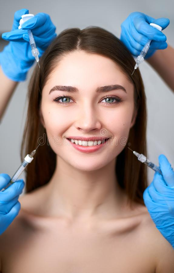 Hands of beauticians holding syringes around flawless woman face ready for injection in cosmetology clinic. Female model royalty free stock photos