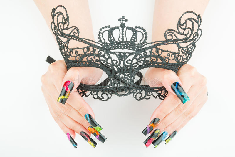 Hands with beautiful manicure holding a black lace carnival mask on white background. Hands with beautiful manicure holding a black lace carnival mask royalty free stock photo