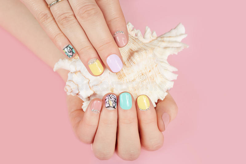 Hands with beautiful manicured nails and sea shell. Hands with beautiful manicured nails different colored with nail polish and sea shell stock photos