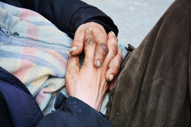 Hands of a beggar in prayer, on the street stock image