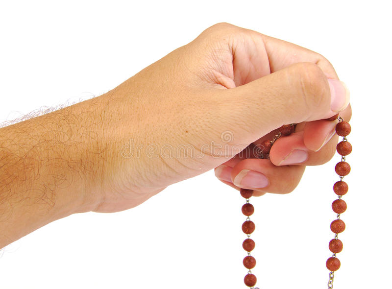 Hands of a believer with wooden rosary stock images