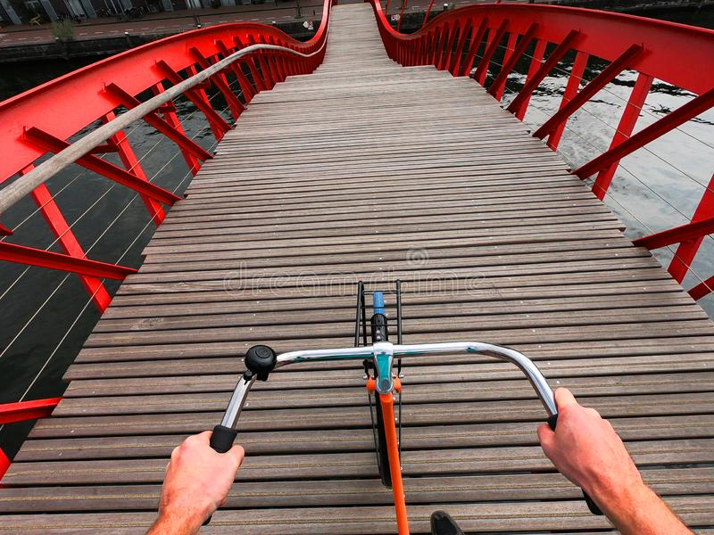 Hands on a Bicycle handlebar POV view. Orange bike on the wooden red Python bridge in Amsterdam, Netherlands royalty free stock photos