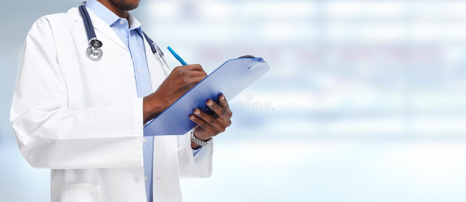 Hands of black doctor man. African-American black doctor man over blue background stock photo