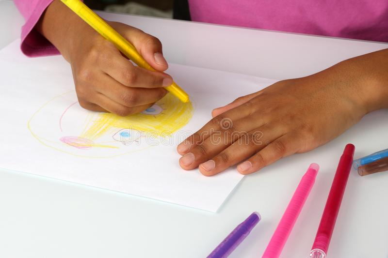 Hands black girls draw a yellow pencil face royalty free stock photo