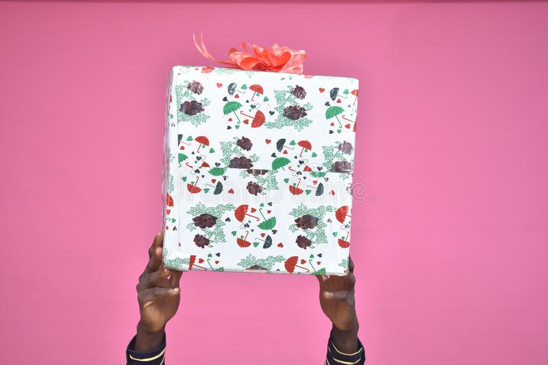 hands only of a black person holding up a big gift box stock images