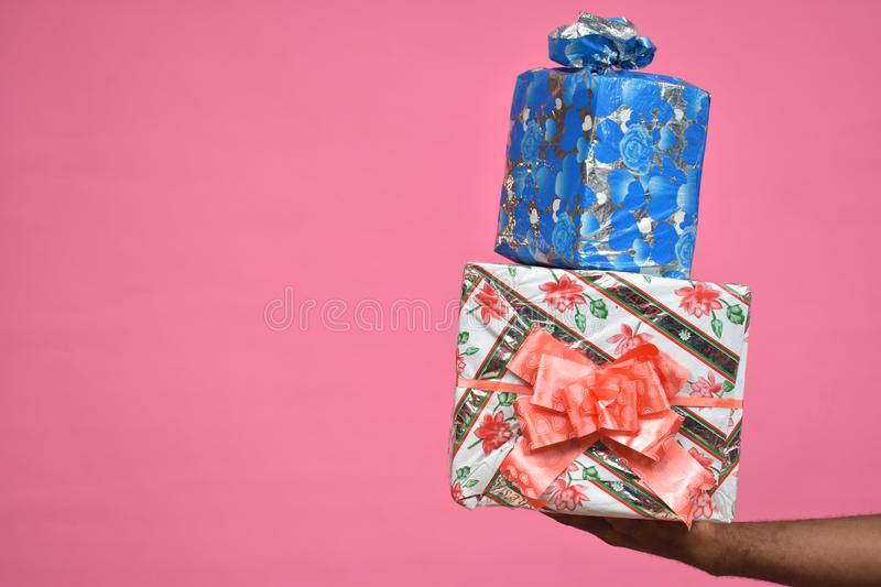 hands only of a black person holding up two gift boxes close up stock images
