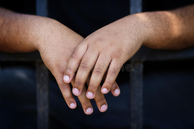 Hands of black prisoner in camera royalty free stock image