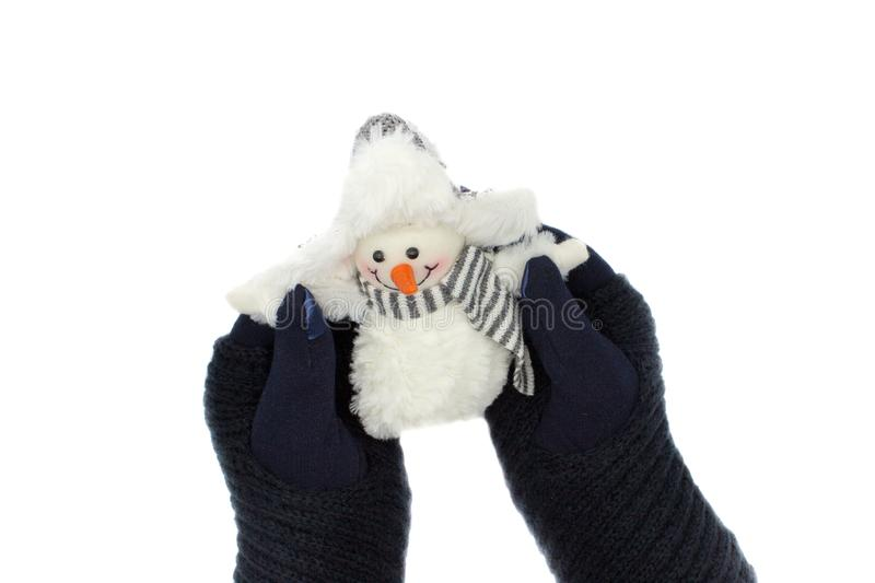 Hands in blue gloves holding a snowman royalty free stock photo