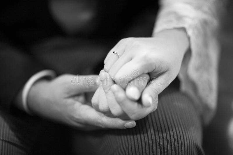 Hands of bride and bridegroom in wedding marriage ceremony. Black and white artistic digital photo of bridegroom in dark suit and white shirt in church religious stock images