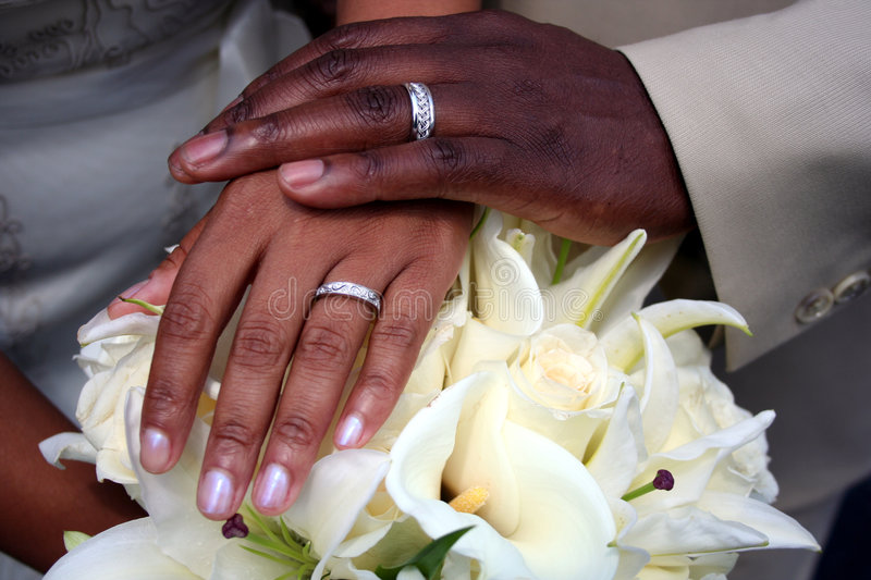 Hands of Bride and Groom. An African-American couple place their hands on a wedding bouquet showing off their wedding bands