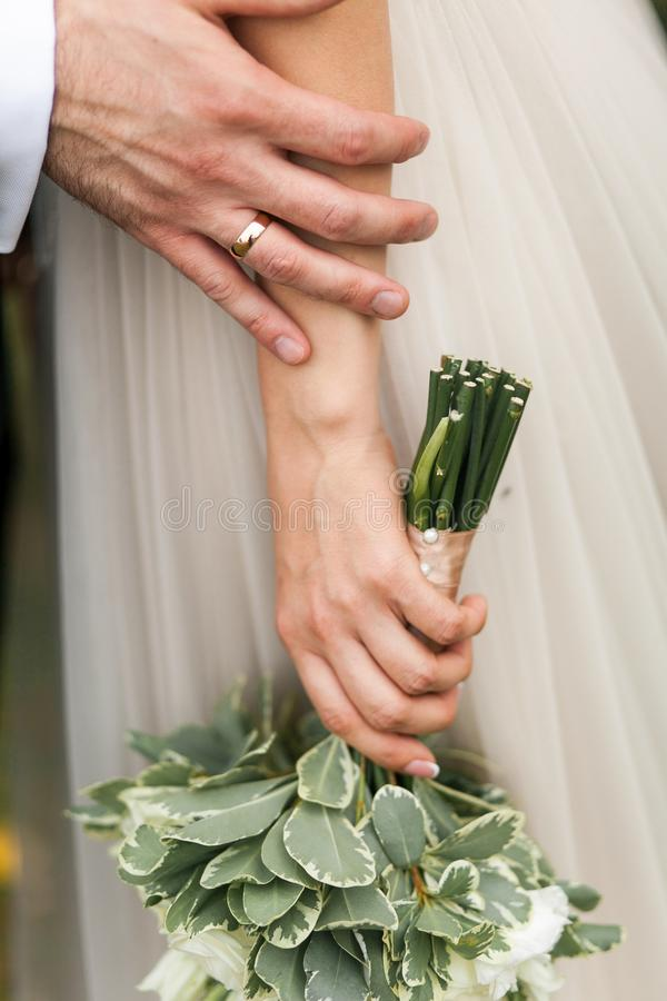 Hands of the bride and groom close-up. The bride is holding a beautiful bouquet of white roses and green leaves. Wedding theme royalty free stock images