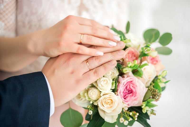 Hands of the bride and groom close up, wearing white gold wedding rings on her hands, the bride is holding a wedding bouquet of stock photography