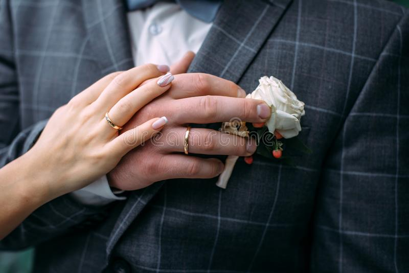 Hands of the bride and groom with elegant manicure, close-up. Wedding rings of the newlyweds, couple on wedding day, touching. Moment royalty free stock photos