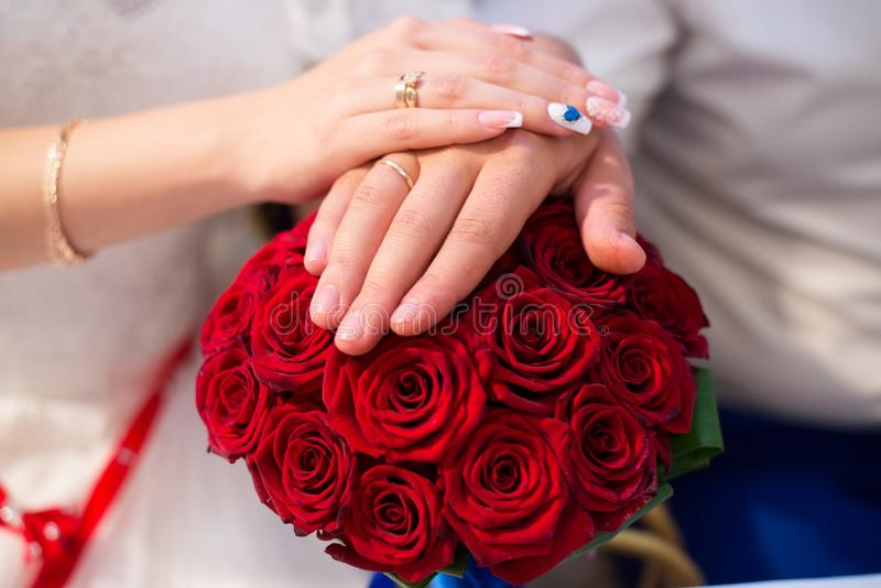 Hands of bride and groom with rings on wedding bouquet. Marriage concept.  stock photos