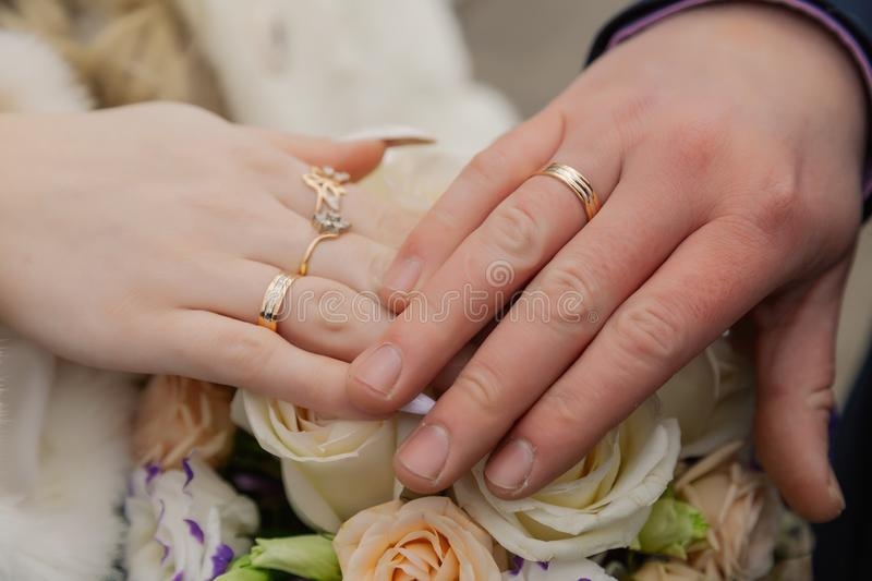 Hands of bride and groom with rings on wedding bouquet. Marriage concept.  stock image