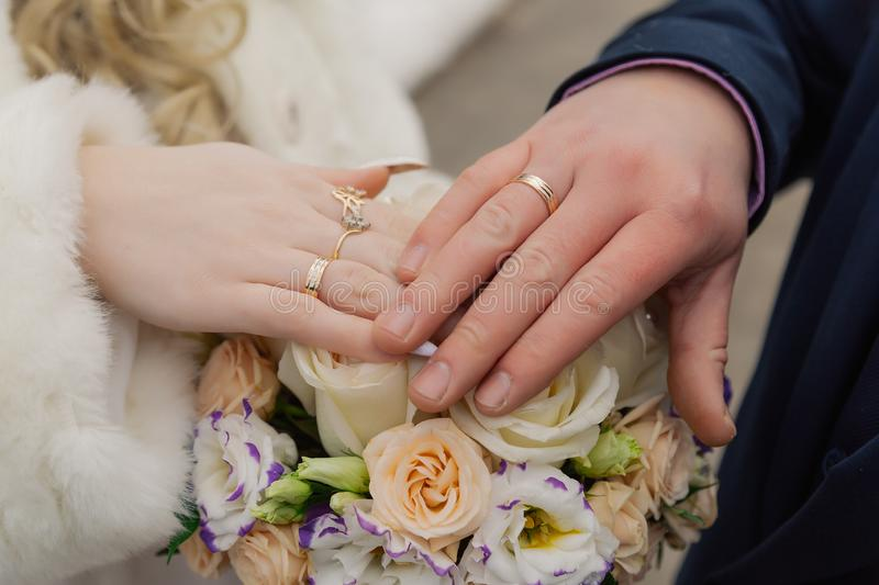 Hands of bride and groom with rings on wedding bouquet. Marriage concept.  royalty free stock photography
