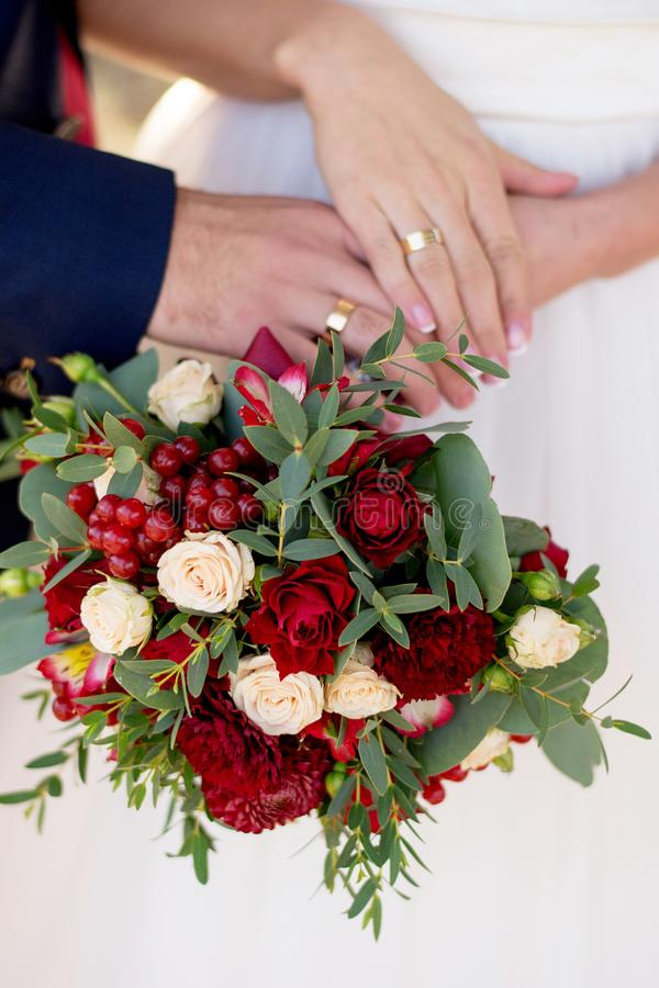 Hands of bride and groom with rings on wedding bouquet. Marriage concept royalty free stock photo