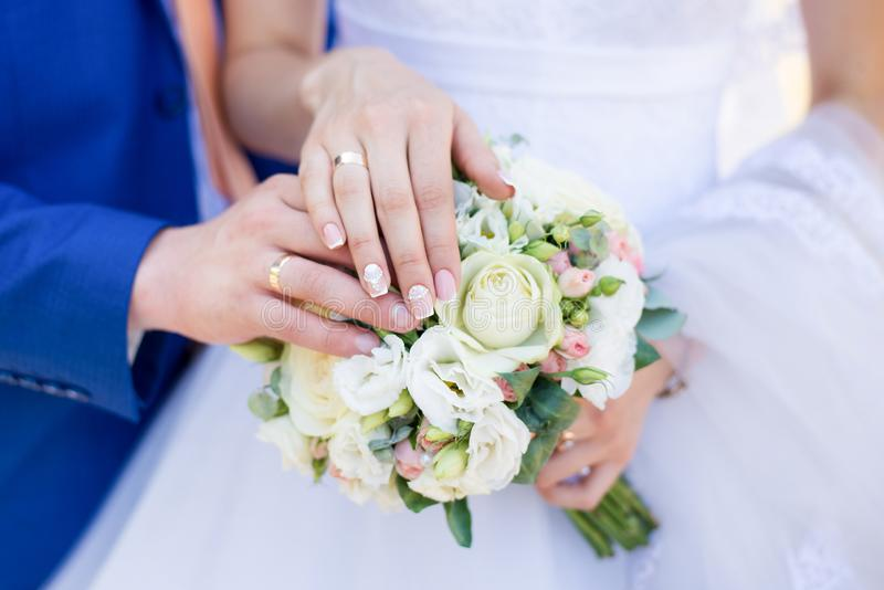 Hands of bride and groom with rings on wedding bouquet. Marriage concept.  stock photography