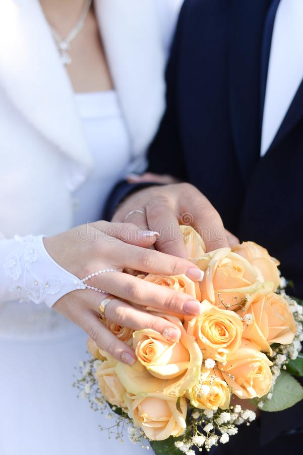 Hands of bride and groom with rings on wedding bouquet. Marriage concept.  royalty free stock photo