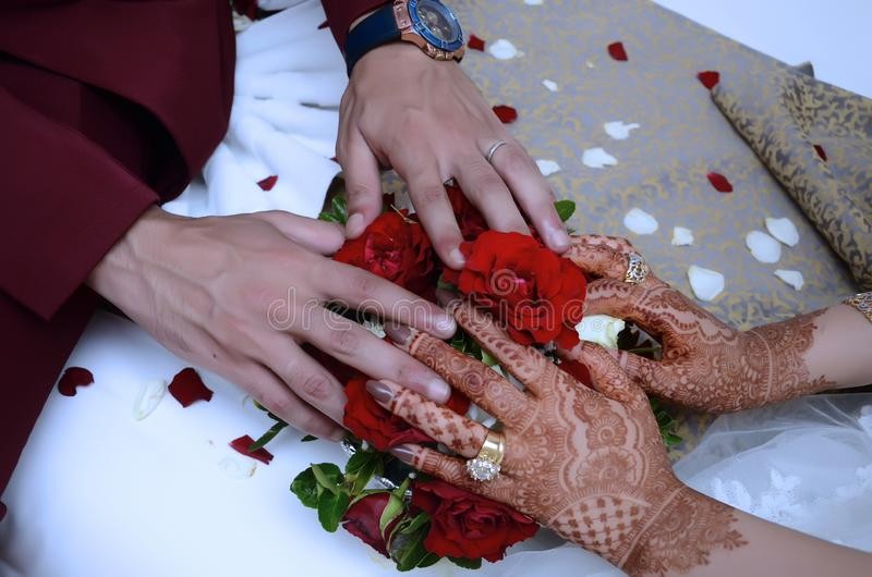 Two hands with gold wedding rings on flower bouquet stock photos