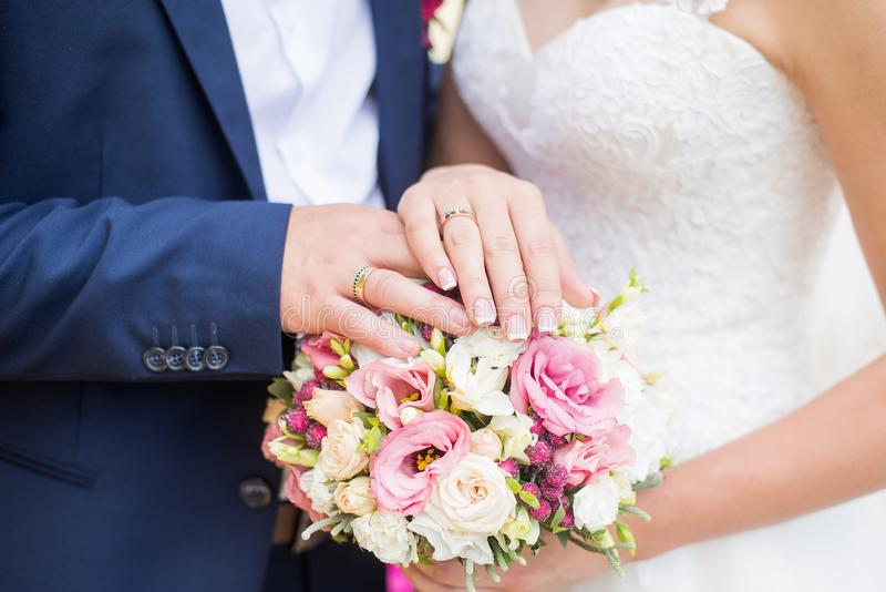 Hands of bride and groom with rings on wedding bouquet. Marriage and love concept.  stock photos