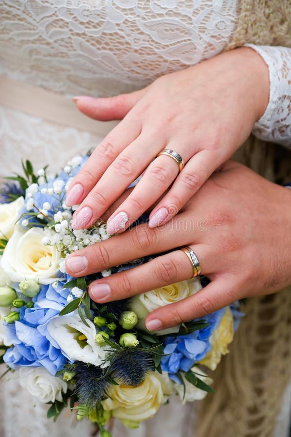 Hands of the bride and groom on the wedding bouquet. Gold wedding rings on the ring fingers of the newlyweds royalty free stock images