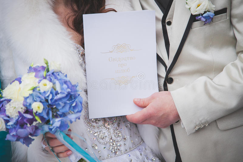 Hands of bride and groom on wedding bouquet. Marriage concept royalty free stock photos