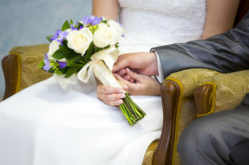 Hands of bride and groom with wedding bouquet of white and violet flowers stock photo