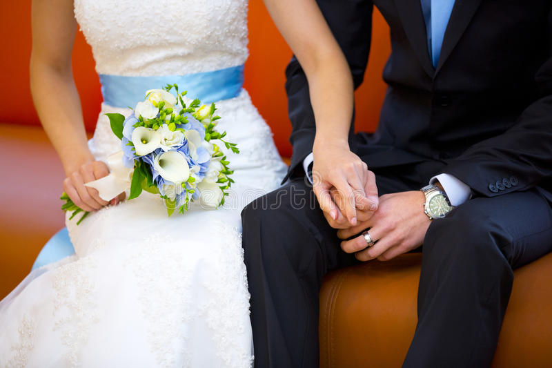 Hands of bride and groom with wedding bouquet. Hands of bride and groom or woman and man with wedding bouquet of white and blue flowers stock image
