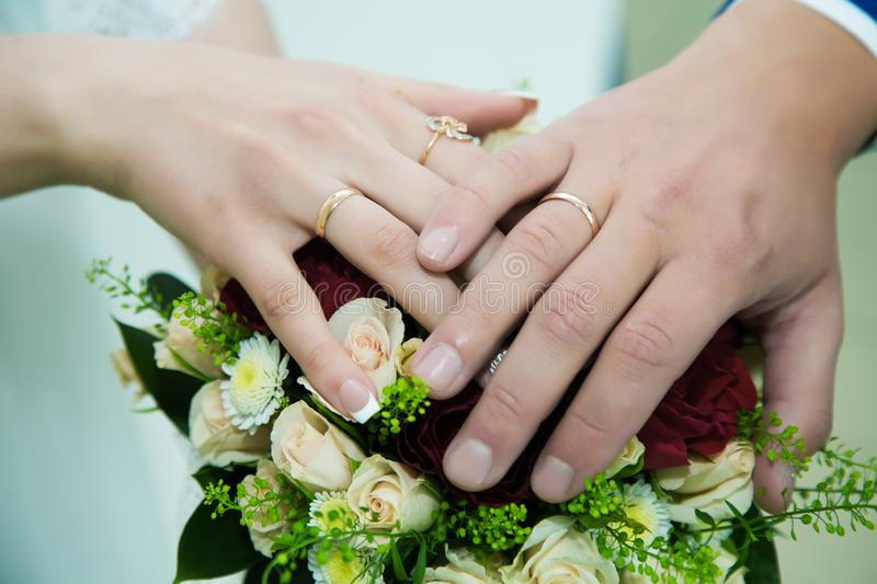 Hands of the bride and groom with wedding rings. On the wedding bouquet stock photo