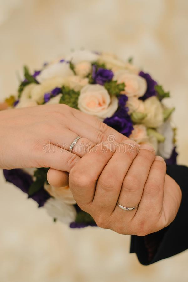 Hands of the bride and groom with wedding rings on the background of a delicate bouquet. stock image