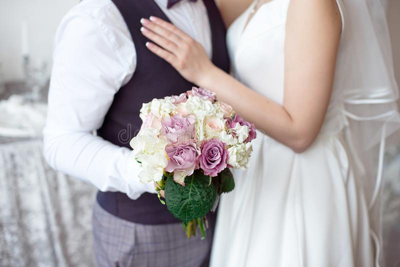 Hands of the bride and groom with wedding rings and a bouquet of flowers stock images