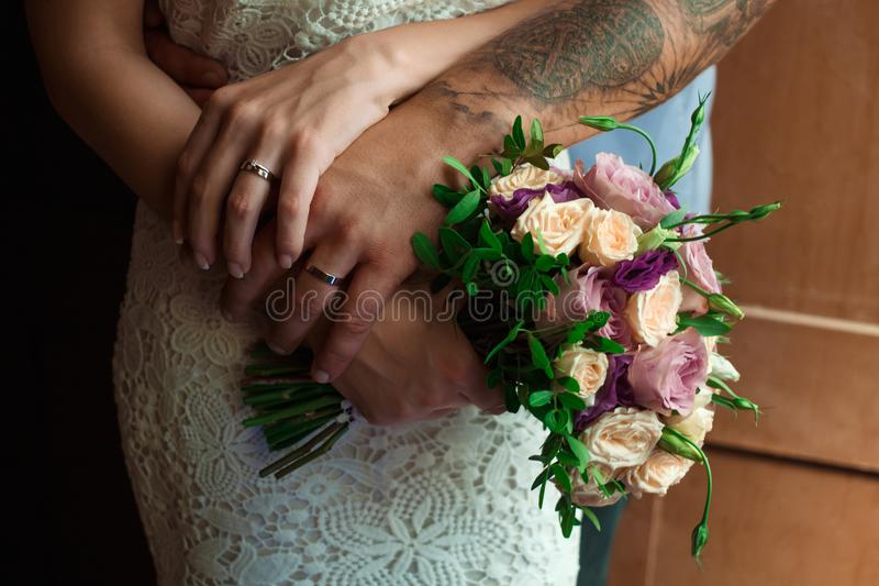 Hands of the bride and groom with wedding rings, bride holds a w. Edding bouquet in hands, the groom hugs her from behind royalty free stock photo