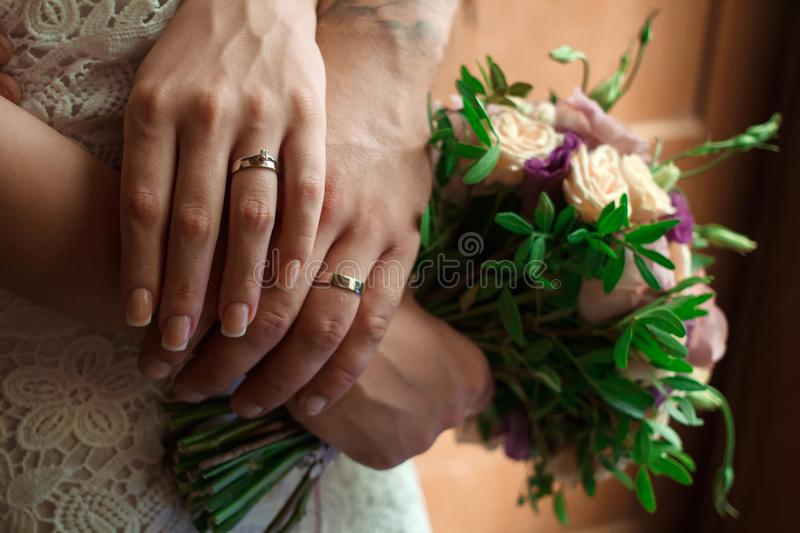 Hands of the bride and groom with wedding rings, bride holds a w. Edding bouquet in hands, the groom hugs her from behind stock photo