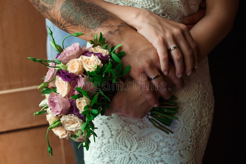 Hands of the bride and groom with wedding rings, bride holds a wedding bouquet in hands, the groom hugs her from behind.  royalty free stock images