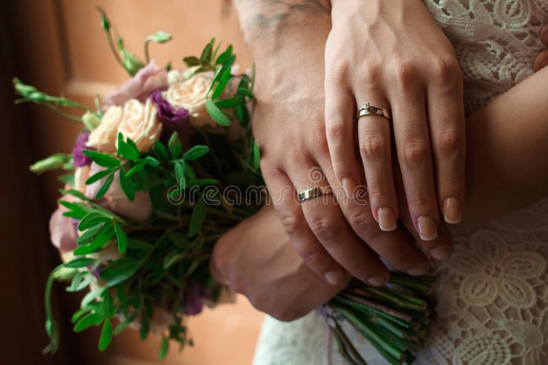 Hands of the bride and groom with wedding rings, bride holds a wedding bouquet in hands, the groom hugs her from behind.  stock images