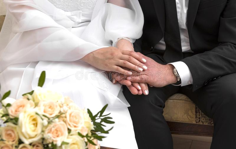 Hands of the bride and groom in a white dress, a bouquet of beige roses royalty free stock photography