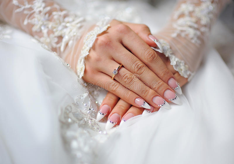 Hands of a bride with a ring and a wedding manicure.  royalty free stock photos