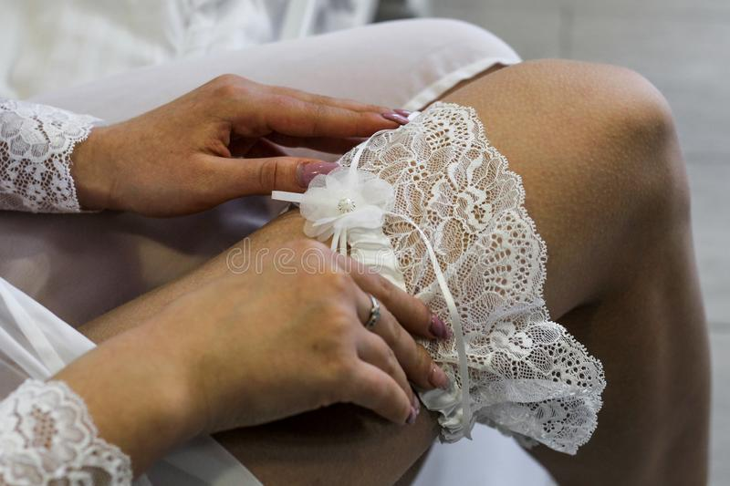 Bridal gowns are lovely white lace wedding garters. Gathering the bride. Hands of the bride straightens white lace wedding garter royalty free stock photography