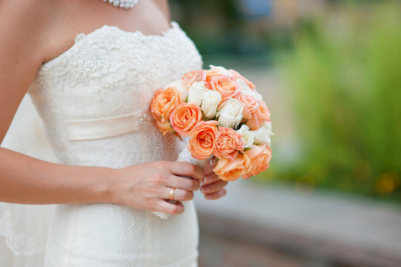 Hands of a bride with a wedding bouquet.  royalty free stock images