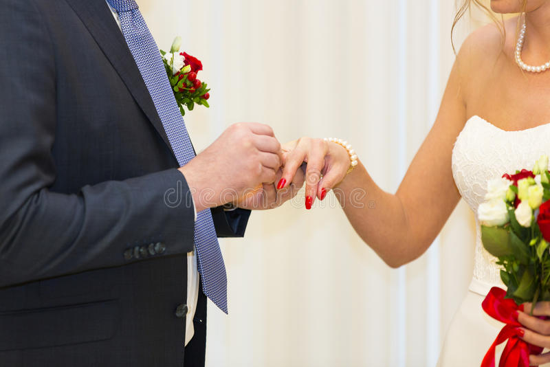 Hands of bride and groom who wear wedding rings to each other. Hands of bride with white and red wedding bouquet and groom in dark suit who wear wedding rings to stock photo