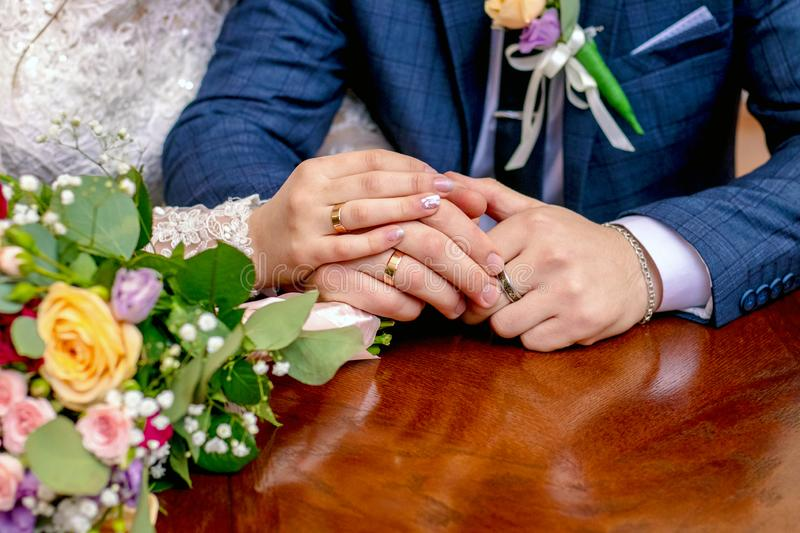 Hands of brides next to a wedding bouquet. The bride put her hand on the groom`s hand_ stock image