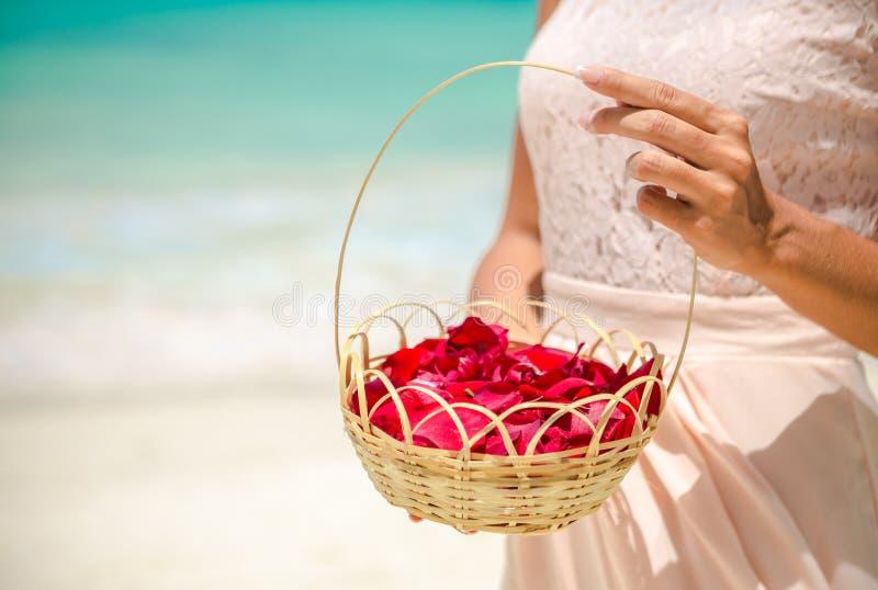 Hands bridesmaid holding a basket of rose petals stock photos
