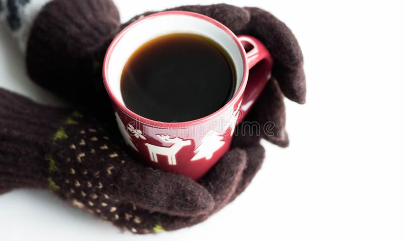 Hands in brown gloves with a New Year pattern hold a red cup with hot coffee on a white background. Top view Flat lay Winter stock photography